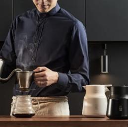 photo lifestyle de la maison japonaise hario, avec un barista qui sert le café grâce à la bouilloire Buono Kettle