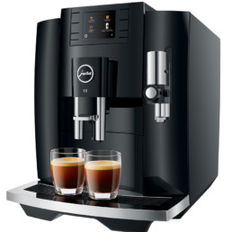 machine à café JURA E8 allumée et présentée avec 2 cafés espressos servis en tasse